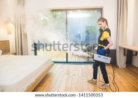 professional cleaning service. woman in uniform and gloves does the cleaning in a cottage. treatment, disinfection of the apartment with hot steam from odors and parasites, bed bugs #1411500353