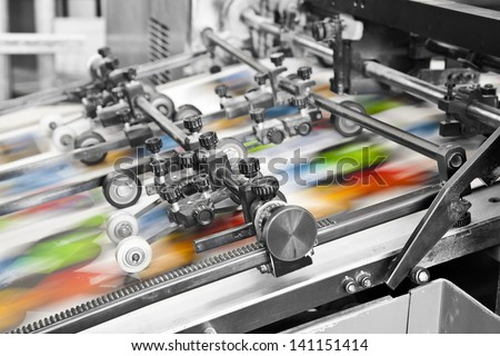 Close up of an offset printing machine during production Royalty-Free Stock Photo #141151414