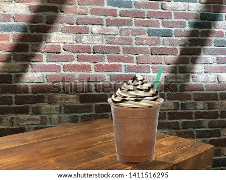Iced coffee or Frappuccino in plastic takeaway or to go cup on wooden table at cafe #1411516295