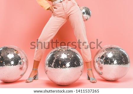 cropped view of fashionable girl posing with disco balls on pink Royalty-Free Stock Photo #1411537265