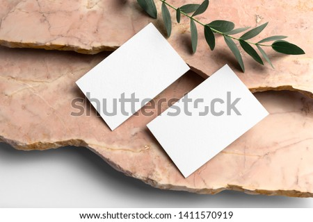 Real photo, business cards branding mockup template, isolated on light grey background, with marble and floral elements to place your design.