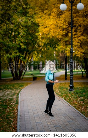 Portrait of a beautiful young woman enjoying autumn in the park. Attractive blonde in the park in autumn against a background of trees with yellow foliage. Sunset photography of the elephant #1411603358