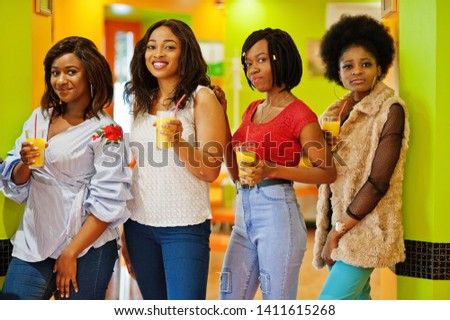 Four young african girls with orange juices pose in bright colored fast food restaurant. #1411615268