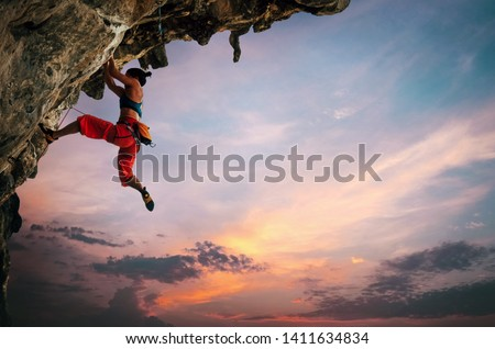 Athletic Woman climbing on overhanging cliff rock with sunset sky background #1411634834