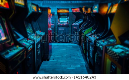 Old Vintage Arcade Video Games in an empty dark gaming room with blue light with glowing displays and beautiful retro design #1411640243