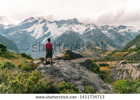 Man hiker admiring view of Mount Cook on the Hooker trail tramping trek. Dramatic adventure. Snow capped Mountain background. Grey cloudy moody. Shot in Pukaki South Island, New Zealand. #1411734713