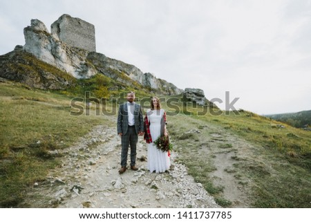 Beautiful bride with a bouquet of flowers and the groom stand and cuddle near the rock. #1411737785