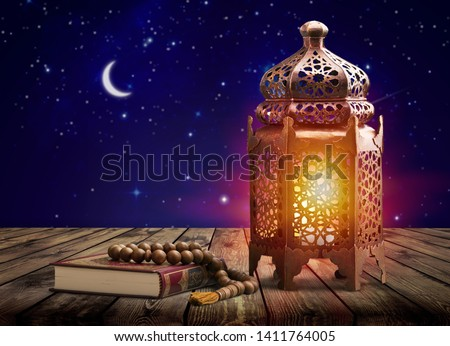 Ornamental dark Moroccan, Arabic lantern and dates on on an old wooden table with the night sky and the Crescent moon and the stars behind. Greeting card for Muslim community holy month Ramadan Kareem #1411764005