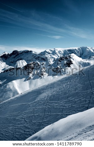Courchevel 1850m. A view from the top of the ski resort looking over mountains in winter  #1411789790