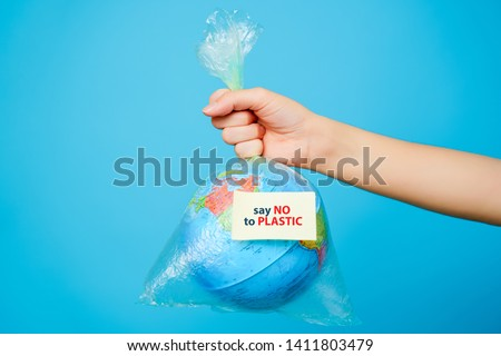 Woman holds in hands plastic bag and planet earth with text sticker-SAY NO TO PLASTIC at blue background. The concept of plastic pollution. #1411803479