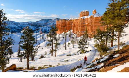 A hiker ventures along the snowy trails of Utah's Bryce Canyon National Park in winter. #1411845422