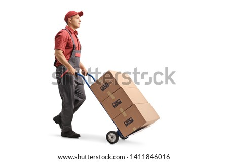 Full length shot of a young male worker in a uniform pushing boxes on a hand truck isolated on white background #1411846016