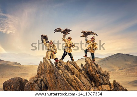 Kazakh Eagle Hunter in traditionally trained golden eagles riding horse in a desert mountain Golden Eagle Festival. Olgei,Western Mongolia. #1411967354