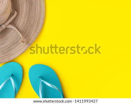Elegant women's straw hat with bow blue slippers on bright sunny yellow background. Beach vacation fashion travel relaxation fun concept. High resolution banner poster with copy space #1411993427