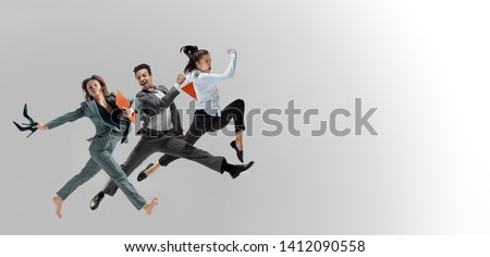 Happy office workers jumping and dancing in casual clothes or suit with folders isolated on studio background. Business, start-up, working open-space, motion and action concept. Creative collage. #1412090558