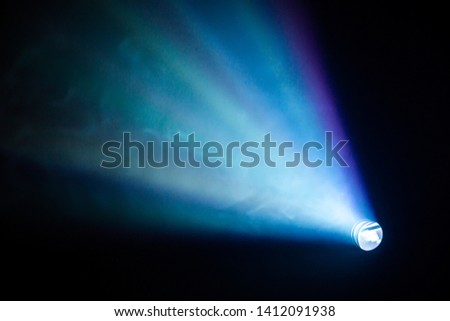 projector spotlight blue color , smoke texture background . light beam screening and glowing for movie cinema and film multimedia production in dark black room at night . wide lens showing, copy space #1412091938