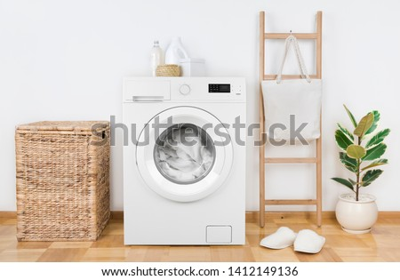 Modern washing machine with basket in laundry room interior #1412149136
