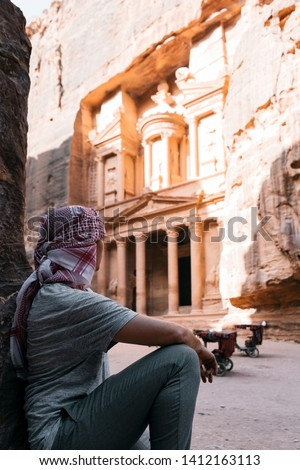 Adventurous man is standing enjoying the beautiful view during a vibrant sunset. Taken on of the Al-Khazneh is one of the most elaborate temples of Petra, Jordan. UNESCO #1412163113