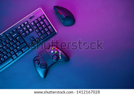 Keyboard, mouse and joystick on violet table background. #1412167028