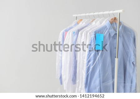 Rack with clothes after dry-cleaning on light background #1412194652