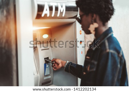 Side view of an African female withdrawing the money from a bank card using street ATM machine; a black girl is inserting her bank card into an automated teller machine to replenish her account #1412202134