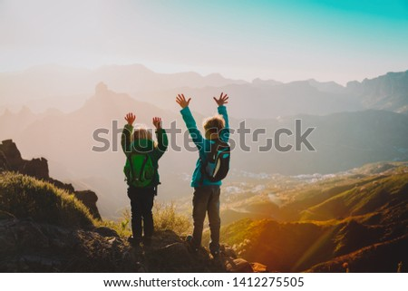 happy boy and girl travel in mountains at sunset #1412275505