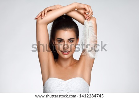 Armpit epilation, hair removal. Young woman holding her arms up and showing clean underarms, depilation smooth clear skin . Beauty portrait. armpit's care. Large white feather near skin #1412284745