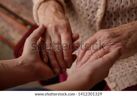 Hands of an old woman and a young man. Caring for the elderly. close up. #1412301329
