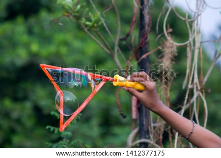 Blowing Bubbles in a garden with green background #1412377175