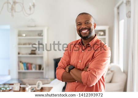 Portrait of smiling mature man with beard standing with crossed arms. Confident african man with folded arms at home looking at camera. Happy senior in casual feeling good. #1412393972