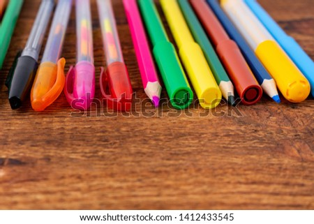 colorful pencils, markers and pens composition mock-up Back to school concept with stationery office supplies on a brown wooden background with copy space close-up #1412433545