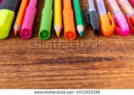 colorful pencils, markers and pens composition mock-up Back to school concept with stationery office supplies on a brown wooden background with copy space close-up #1412433548