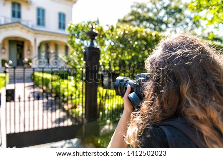 New Orleans, USA Old historic Garden district in Louisiana with green spring summer day and woman photographer taking picture of house with camera