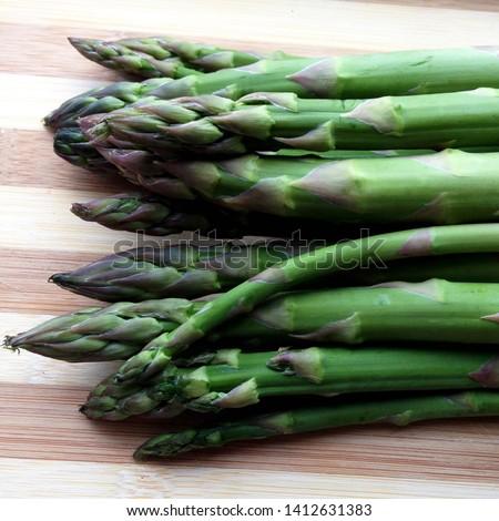 Macro Photo food vegetable asparagus. Texture background of green fresh asparagus sticks. Image of product vegetable stems of green asparagus on wooden board #1412631383