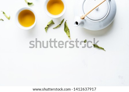 Asian tea concept, two white cups of tea and teapot surrounded with green tea dry leaves view from above, space for a text on white background. #1412637917