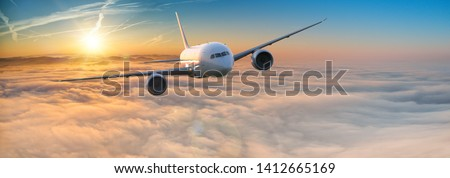 Commercial airplane jetliner flying above dramatic clouds in beautiful light. Travel concept. #1412665169