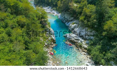 AERIAL: Flying towards a group of tourists whitewater rafting on the breathtaking emerald river rushing through the untouched wilderness in Slovenia. Scenic view of Soca river in the summertime. #1412668643