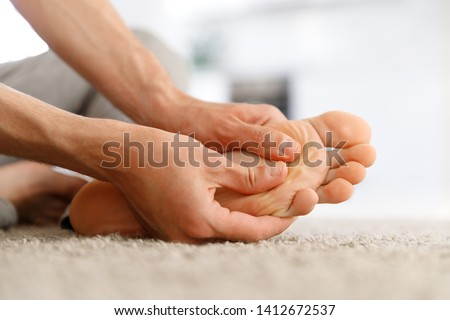 Man hands giving foot massage to yourself to relieve pain after a long walk, suffering with flat feet, close up, soft focus, indoors. Flat feet, leg fatigue.   #1412672537