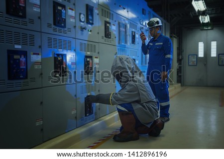 Electrical worker wearing arc flash suit protection is used to draw out a large circuit breaker. Royalty-Free Stock Photo #1412896196