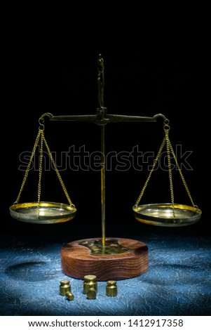 Old vintage scales of justice with weights stand on a stone background. Picture taken with a light brush - Image