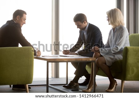 Male business partners sign contract after successful office briefing, making agreement on cooperation, businessmen put signature, closing deal negotiate over collaboration. Partnership concept #1412966471
