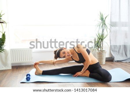 Smiling woman in sportswear exercising on fitness mat and looking at camera in living room  #1413017084