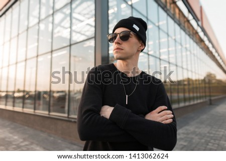 Nice young handsome hipster man in stylish knitted black hat in trendy trendy sunglasses in a t-shirt posing on the background of a modern glass building in the city. American attractive guy. Style. #1413062624
