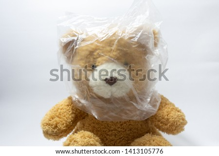 A brown bear doll was covered by plastic bag, plastic bag is bad for wild animal. Say no to plastic bag. #1413105776