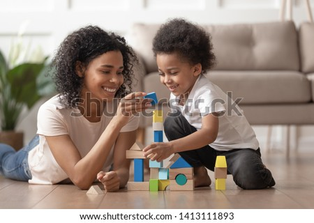 Smiling african mother baby sitter play with little kid son lay on warm floor, caring black mother nanny help teach child boy build constructor of wooden blocks at home, daycare, children development #1413111893