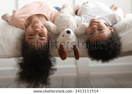 Funny cute little boy and girl laughing lying upside down on bed with toy, happy cheerful kids brother with sister having fun together looking at camera in bedroom, children siblings portrait