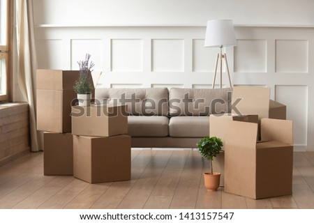 Moving day concept, cardboard carton boxes stack with household belongings in modern house living room, packed containers on floor in new home, relocation, renovation, removals and delivery service #1413157547