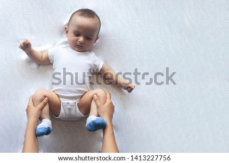 Newborn baby massage. Mom doing gymnastics with kid. Mommy massaging her cute baby boy. Moving a baby's legs, relieve constipation. Mother doing exercises and movements to stimulate a baby's bowels. #1413227756