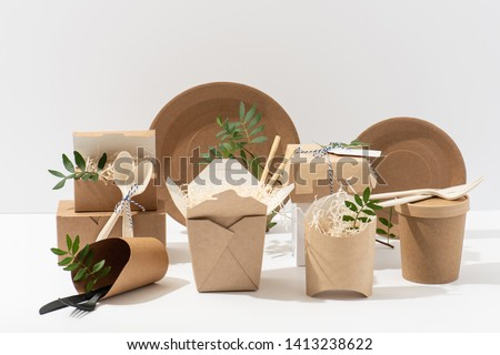 Eco friendly, disposable, recyclable, compostable tableware. Paper food boxes, dishes and flower pots with saw shawings and rowan branches in them and cornstarch cutlery over white background #1413238622