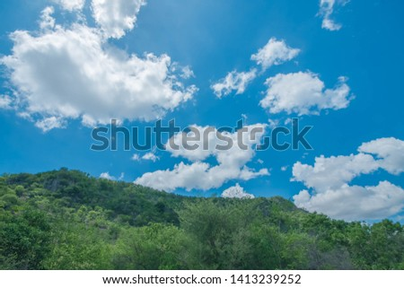 Bright sky during the day light hours, the hot, fluffy, white and feeling free and gray clouds float around the vast sky. A panoramic view beside the road and mountain looking and feeling free.  #1413239252